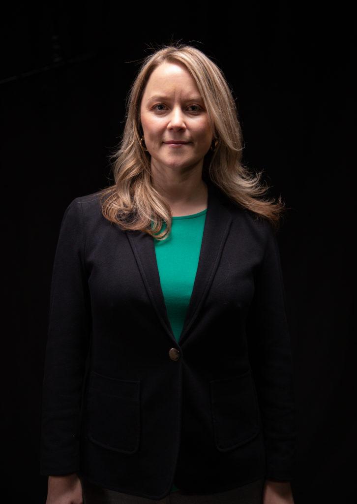 White female professor standing for portrait.